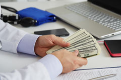 Мужской доктор медицины держа в пуке рук 100 долларов b Стоковая Фотография RF