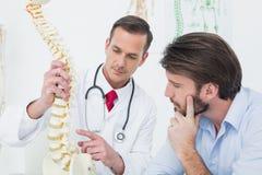 Мужской доктор объясняя позвоночник к пациенту стоковое фото rf