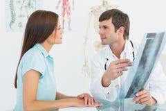 Мужской доктор объясняя рентгеновский снимок позвоночника к женскому пациенту Стоковое фото RF