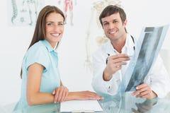 Мужской доктор объясняя рентгеновский снимок позвоночника к женскому пациенту Стоковые Фотографии RF