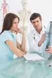Мужской доктор объясняя рентгеновский снимок позвоночника к женскому пациенту Стоковые Изображения RF