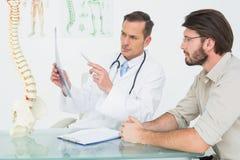Мужской доктор объясняя рентгеновский снимок позвоночника к пациенту Стоковое Изображение RF