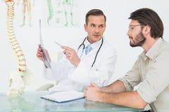 Мужской доктор объясняя рентгеновский снимок позвоночника к пациенту Стоковые Фотографии RF