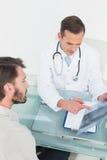Мужской доктор объясняя рентгеновский снимок позвоночника к пациенту Стоковая Фотография