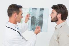 Мужской доктор объясняя рентгеновский снимок позвоночника к пациенту Стоковые Изображения