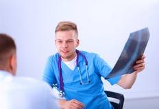 Мужской доктор объясняя рентгеновский снимок позвоночника к пациенту внутри Стоковые Изображения