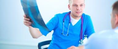 Мужской доктор объясняя рентгеновский снимок позвоночника к пациенту в медицинском офисе Стоковое фото RF