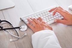 Мужской доктор печатая на клавиатуре компьютера стоковая фотография
