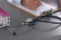 Мужской доктор пишет на столе с пробиркой Стоковое Изображение RF
