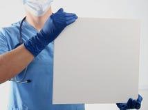 Мужской доктор показывая доску сзажимом для бумаги с космосом экземпляра для текста Стоковые Изображения RF