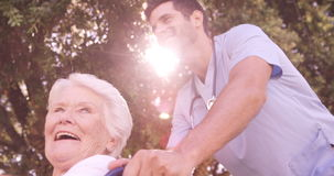 Мужской доктор помогая старшей женщине на кресло-коляске в задворк сток-видео