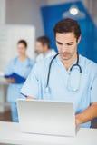 Мужской доктор работая на компьтер-книжке при коллеги обсуждая Стоковая Фотография RF
