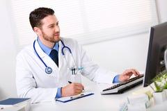 Мужской доктор работая на компьютере Стоковые Фотографии RF
