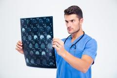 Мужской доктор смотря изображение рентгеновского снимка мозга Стоковое Изображение