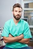 Мужской доктор с бородой в зеленом костюме в зубоврачебной клинике Стоковые Изображения RF