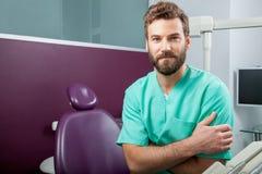 Мужской доктор с бородой в зеленом костюме в зубоврачебной клинике Стоковое фото RF