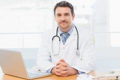 Мужской доктор с компьтер-книжкой на столе в медицинском офисе Стоковое Изображение RF