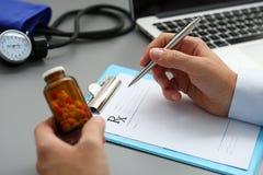 Мужской опарник владением руки доктора медицины пилюлек и пишет prescripti Стоковое Изображение RF