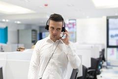 Мужской оператор центра телефонного обслуживания делая его работу стоковые фотографии rf