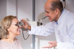 мужской офтальмолог и женский пенсионер проверяя зрение в клинике Стоковое Изображение RF