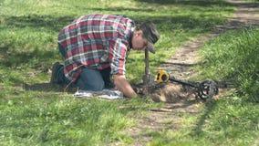 Мужской охотник за сокровищами вытягивает вне старые монетки найденные на поле с металлоискателем акции видеоматериалы