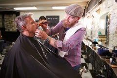 Мужской парикмахер давая бритье клиента в магазине Стоковое Изображение RF