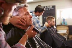 Мужской парикмахер давая бритье клиента в магазине Стоковые Изображения RF