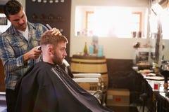 Мужской парикмахер давая стрижку клиента в магазине Стоковое Изображение