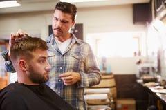 Мужской парикмахер давая стрижку клиента в магазине Стоковые Фото