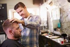 Мужской парикмахер давая стрижку клиента в магазине Стоковое Фото