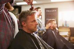 Мужской парикмахер давая стрижку клиента в магазине Стоковая Фотография RF