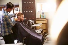 Мужской парикмахер давая стрижку клиента в магазине Стоковая Фотография