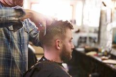 Мужской парикмахер давая стрижку клиента в магазине Стоковое фото RF