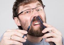 Мужской парикмахер режет его собственные волосы в носе, смотря камеру как зеркало стильный профессиональный парикмахер Стоковые Изображения