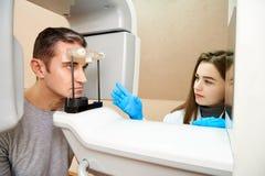 Мужской пациент в блоке развертки, и девушк-доктор около пульта управления Зубоврачебная томография стоковые фото