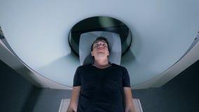 Мужской пациент в томографическом блоке развертки, взгляд сверху сток-видео