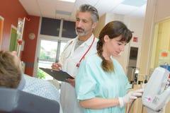 Мужской пациент доктора и медсестры посещая на больнице Стоковое Изображение RF