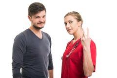 Мужской пациент и женский доктор показывая номер два Стоковое фото RF
