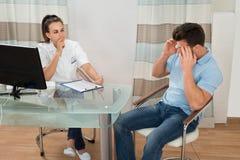 Мужской пациент с молодым женским доктором На Клиникой стоковое изображение