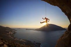 Мужской падать альпиниста утеса скалы на заходе солнца Стоковая Фотография
