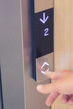 Мужской палец отжимая вниз с кнопки лифта стрелки стоковое фото rf