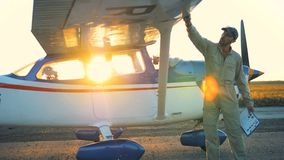 Мужской пилот очищает самолет во время захода солнца сток-видео