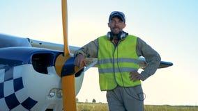 Мужской пилот стоит около светлого частного самолета Персона стоит около малого самолета, смотря и усмехаясь на камере акции видеоматериалы