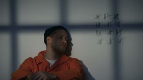 Мужской пленник смотря пересеченные линии на клеточной оболочке, служа длинное заточение видеоматериал