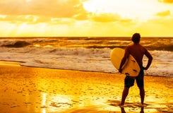 Мужской пляж восхода солнца захода солнца серфера & Surfboard человека Стоковая Фотография