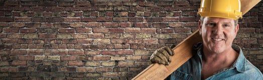 Мужской подрядчик в трудной шляпе держа деревянную планку перед старым знаменем кирпичной стены с космосом экземпляра стоковое изображение