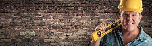 Мужской подрядчик в уровне удерживания трудной шляпы перед старым знаменем кирпичной стены с космосом экземпляра стоковые изображения
