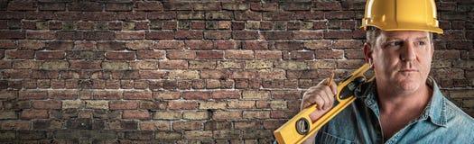Мужской подрядчик в уровне удерживания трудной шляпы перед старым знаменем кирпичной стены с космосом экземпляра стоковые изображения rf