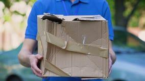 Мужской показ курьера повредил коробку, дешевую поставку пакета, плохое качество пересылки сток-видео