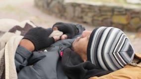 Мужской попрошайка спать на стенде и просыпая вверх, беспризорность, живя в бедности сток-видео